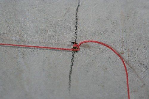 Натягиваем нить по горизонтали в верхней части стены.