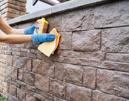 Процесс обработки искусственного камня защитным раствором после его укладки.