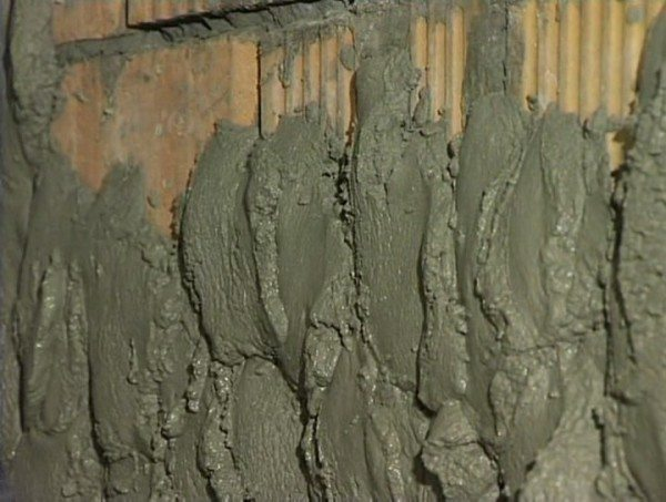Раствор сперва набрасывают на стену ковшиком.